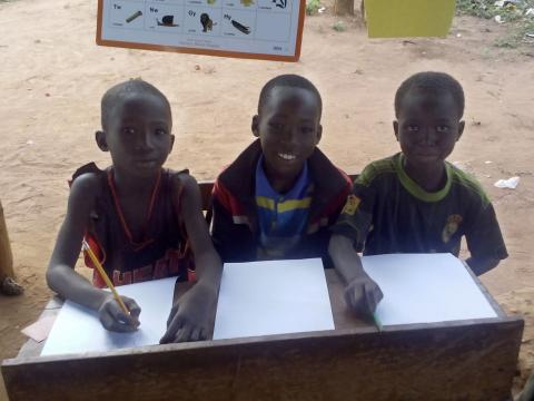 Children smile at a Literacy Boost reading club in Ghana