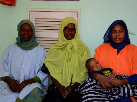 Mariem(in the left), sitting next to the Aminata, mother of baby Ibrahim, 2 months old , whom she helped giving birth, and Mama Aisha a retired cook who became volunteer with her at the Deba Hijaj Health center : Coumba Betty Diallo, © World Vision 2016.