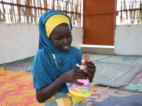 Fanna playing with her doll in the Child Friendly Space of Sayam Forage in Diffa, Niger