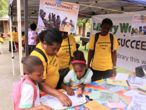 Teachers and students try the spelling activity at the World Vision booth.