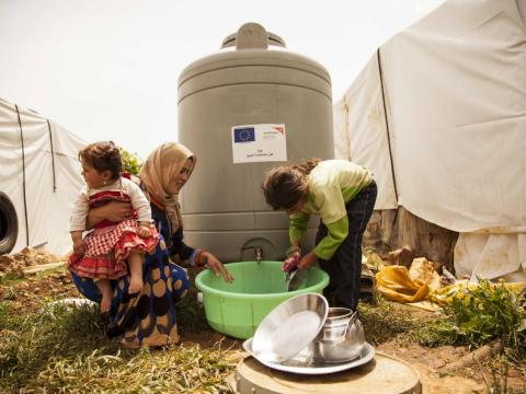 A family wash dishes at a water tank in a informal refugee settlement in Lebanon's Bekaa Valley.