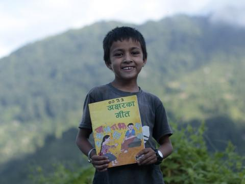 Child holds mother language book