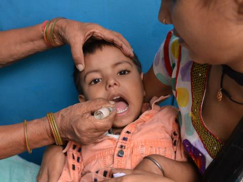Yash, a sponsored child, getting his routine polio drops from a community health worker