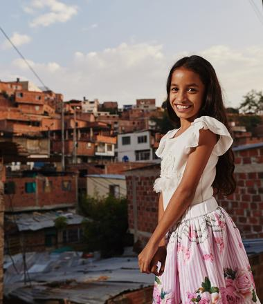 A Colombian girl stands in her village