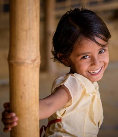 A girl smiles while holding a support beam in her home