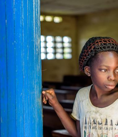 A young girl stands at her school in DRC