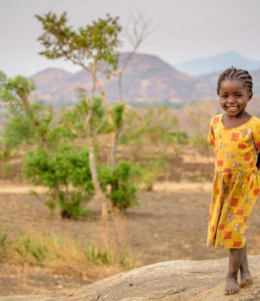 A girl in Malawi stands in a field