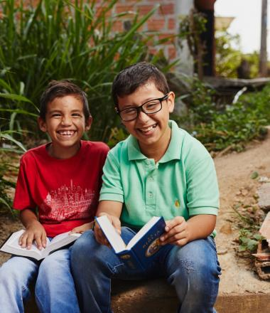 Two Colombian boys reading a book