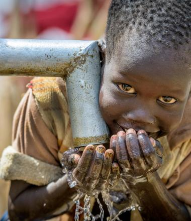 A Sudanese boy drinking clean water