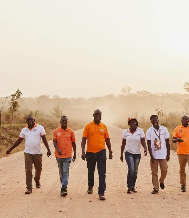 World Vision employees walk down a road in Ghana