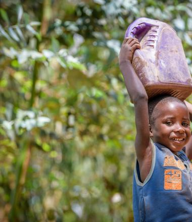 Rwandan girl carries water home