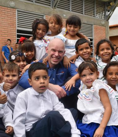 WVI President Andrew Morley sits with children in Colombia