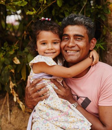 A father holds his daughter in rural Colombia