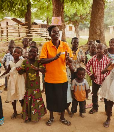 A World Vision employee sings with a group of children
