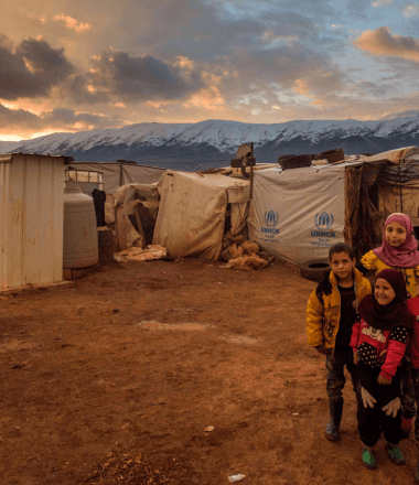 Children standing upfront of Syrian refugee camp