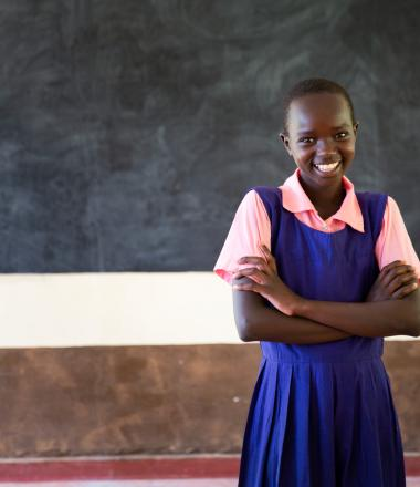 A girl standing proudly at her school