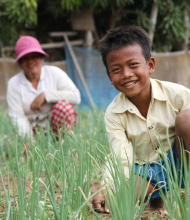 Khmer boy in the foreground kneeling in a grassy field with his mum in the background