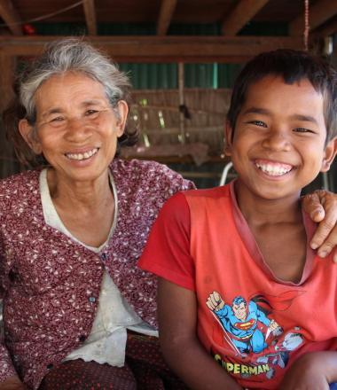 12 year old Khmer boy sits with his grandmother, they are both smiling at the camera.