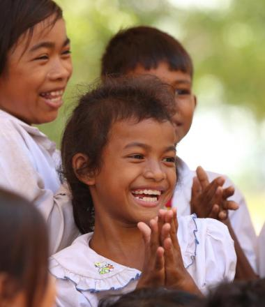 Cambodian girl smiling with student peers around her all clapping their hands with joy.