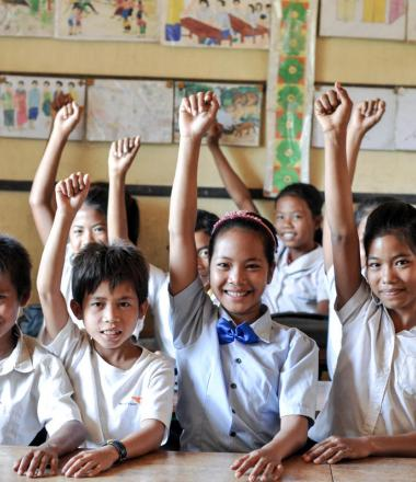 Group of Khmer students smiling with their hands raised in the air sitting at desks inside a classroom