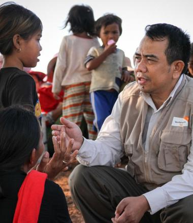World Vision Cambodia staff member listening to flood affected child from rural village, Cambodia
