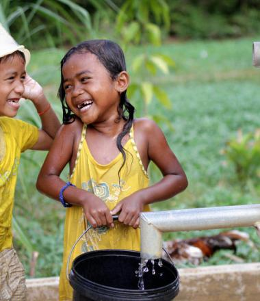 Khmer boy and girl laughing at each other playing in water from pump installed by World Vision Cambodia.