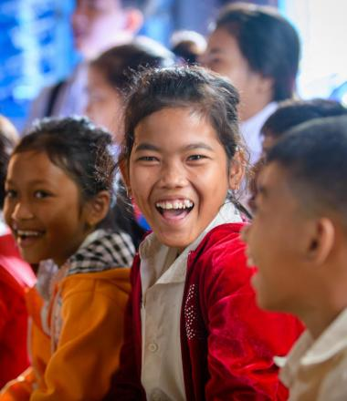 Group of Khmer children sitting on the floor of a classroom with one ecstatic girl looking directly at the camera