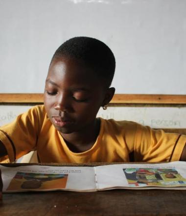 Child in yellow shirt reading book at school