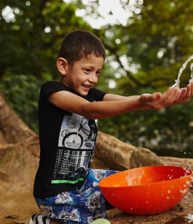 Boy splashing clean water from orange bowl