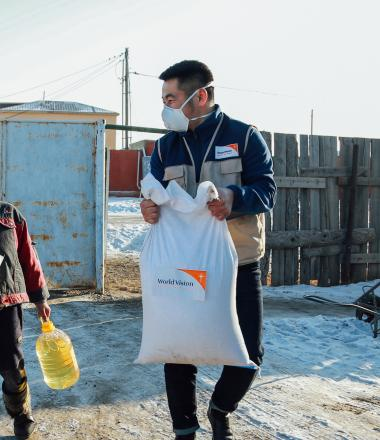 World Vision staff distributing food to child in mask