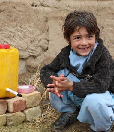 Samiullah is happy to use the water from hand washing station.