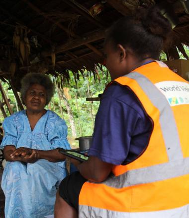 A World Vision enumerator speaking to community member as part of the water, women and disability study