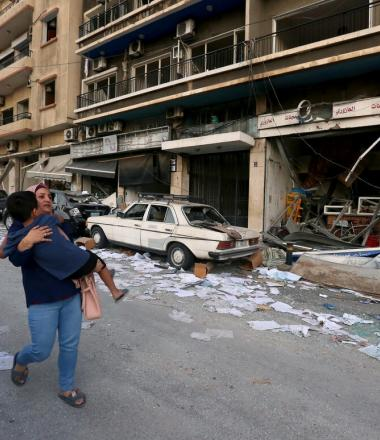 Parent carries child through the rubble in Beirut following deadling blast