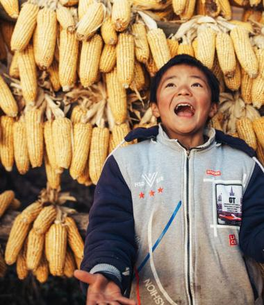 Child in China joyfully standing in front of backdrop of corn