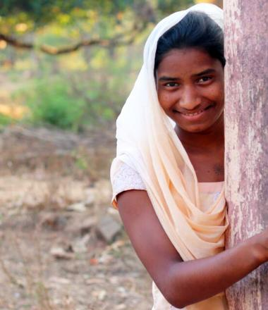 Rashmi from India, girl child behind a tree