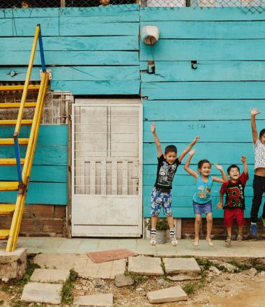 Children jumping upfront of blue wall