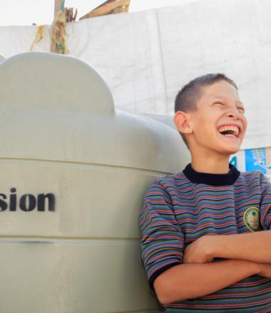 Boy smiling, leaning against water tank