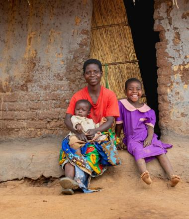 Woman sits with her children in front of her house with her children in Africa
