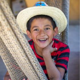 A boy in Mexico smiles while sitting in a hammock