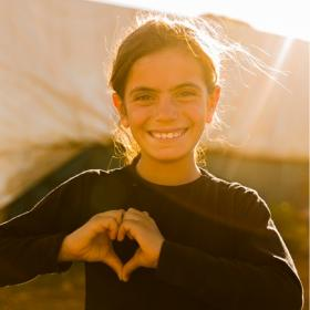 A girl makes a heart shape with her hands