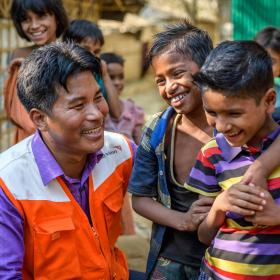 A World Vision employee smiles with some children in Bangladesh