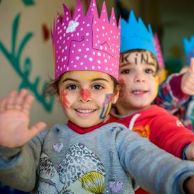 Children with face paint wearing crowns