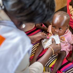 A baby receives a food pouch from a World Vision worker in Africa