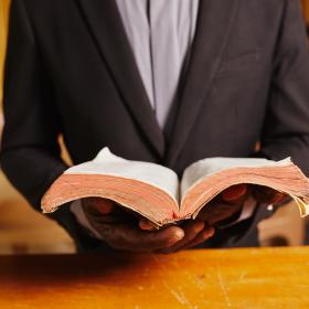 A Pastor in Ghana holds his Bible