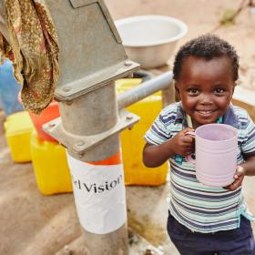 A boy in Ghana drinks water from a World Vision well.