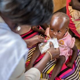 Little girl being fed by World Vision worker