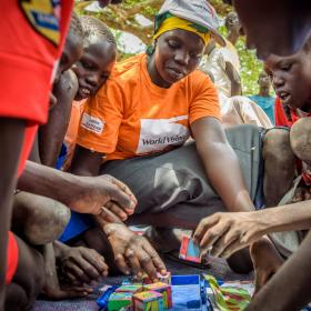 World Vision staff playing a game with children