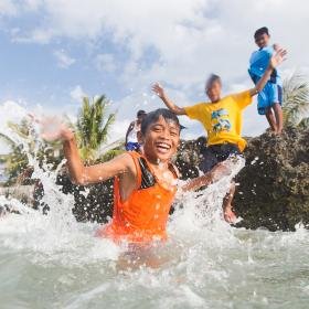 A group of children jump into the ocean in the Philippines