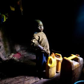 A young Burundi child stands in his home