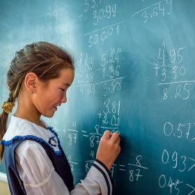 A young girl writes on a chalkboard